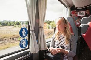 Teenage girl sitting on trainの写真素材 [FYI02856538]