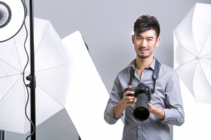 Photographer standing in studio with cameraの写真素材 [FYI02856551]