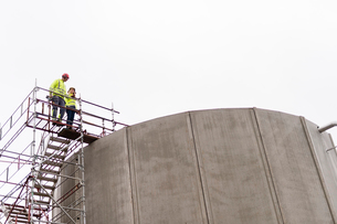 Sweden, Vastmanland, Man and woman standing on scaffolding by water treatment plantの写真素材 [FYI02856556]