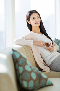 Happy young woman drinking black teaの写真素材 [FYI02856596]