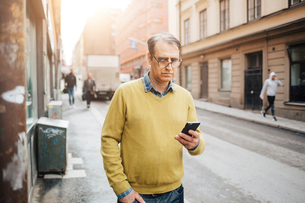 Man holding a smart phone on a street in Stockholmの写真素材 [FYI02856613]