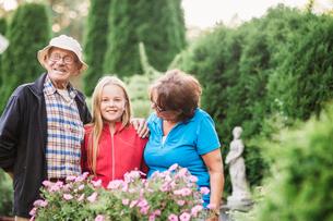 Sweden, Vastmanland, Hallefors, Bergslagen, Girl (12-13) with grandparents posing in gardenの写真素材 [FYI02856614]
