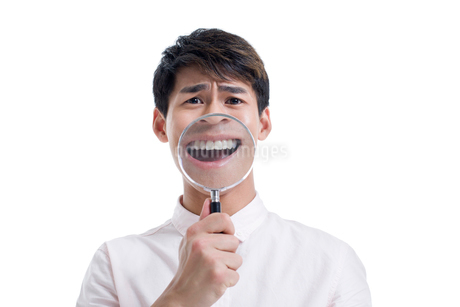 Young man holding a magnifying glass in front of his mouthの写真素材 [FYI02856625]