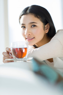 Happy young woman drinking black teaの写真素材 [FYI02856626]