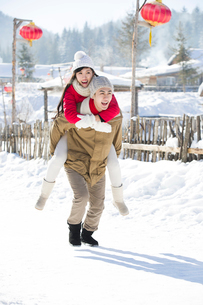 Young man giving his girlfriend piggyback in the snowの写真素材 [FYI02856632]