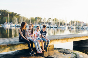 Boys and girls sitting on a pier in a marina in Blekinge, Swedenの写真素材 [FYI02856635]