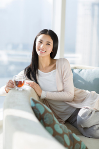 Happy young woman drinking black teaの写真素材 [FYI02856643]