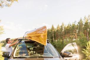 Sweden, Vastmanland, Hallefors, Bergslagen, Man standing by car with kayak on roofの写真素材 [FYI02856656]