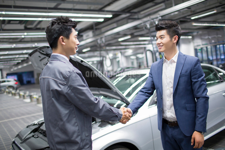 Auto mechanic and car owner shaking handsの写真素材 [FYI02856686]