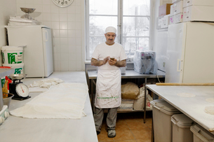 Chef holding smart phone in kitchenの写真素材 [FYI02856689]