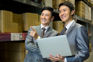 Business partners with laptop in logistic warehouseの写真素材 [FYI02856690]