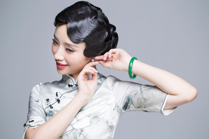 Young beautiful woman in traditional cheongsam dressing up herselfの写真素材 [FYI02856691]
