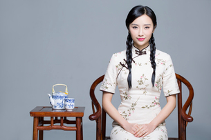 Young beautiful woman in traditional cheongsam with tea setの写真素材 [FYI02856704]