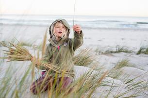 Girl playing with grass on Sandhammaren in Swedenの写真素材 [FYI02856713]