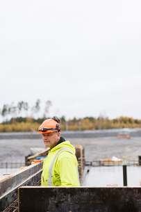 Sweden, Vastmanland, Construction worker looking away at construction siteの写真素材 [FYI02856721]