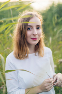 Young woman standing in a field of grass in Karlskrona, Swedenの写真素材 [FYI02856725]
