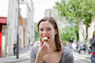 France, Ile-de-France, Paris, Young woman eating cookieの写真素材 [FYI02856732]