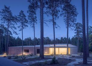 Sweden, Sodermanland, Stockholm, Gamla Enskede, Skogskyrkogarden, Illuminated building among trees aの写真素材 [FYI02856744]