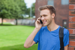 Smiling handsome student leaning against wall phoningの写真素材 [FYI02856749]