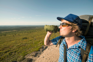 Man drinking from a bottle at the Pallas-Yllastunturi National Park in Lapland, Finlandの写真素材 [FYI02856771]