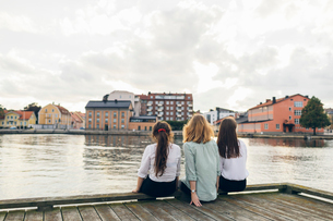 Three young women sitting on a pier in Karlskrona, Swedenの写真素材 [FYI02856827]