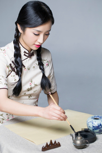 Young beautiful woman in traditional cheongsam practicing calligraphyの写真素材 [FYI02856833]