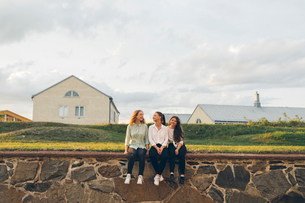 Three young women sitting on a wall in Karlskrona, Swedenの写真素材 [FYI02856836]