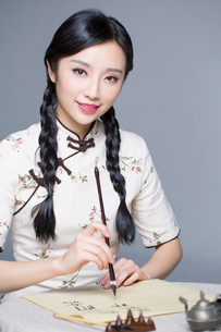 Young beautiful woman in traditional cheongsam practicing calligraphyの写真素材 [FYI02856842]
