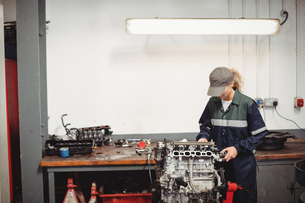 Female mechanic checking a car partsの写真素材 [FYI02856845]