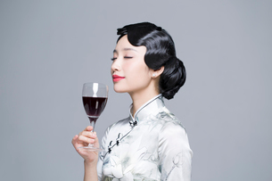 Young beautiful woman in traditional cheongsam with red wineの写真素材 [FYI02856851]