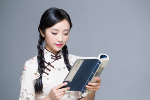 Young beautiful woman in traditional cheongsam reading bookの写真素材 [FYI02856855]