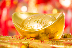 Chinese traditional currency yuanbao and firecrackersの写真素材 [FYI02856857]