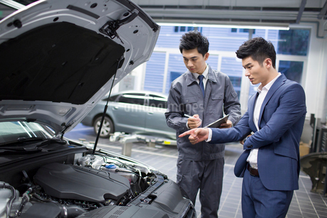 Auto mechanic talking with car ownerの写真素材 [FYI02856864]