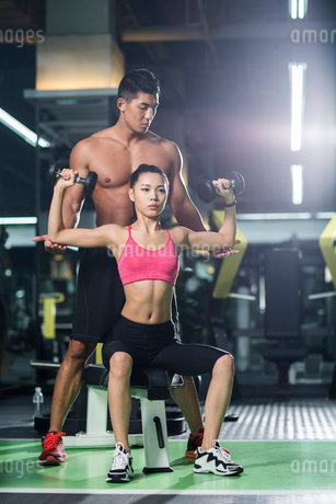 Young woman working with trainer at gymの写真素材 [FYI02856869]