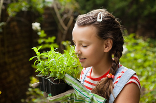 Girl with eyes closed smelling potted plantsの写真素材 [FYI02856874]