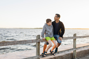 Father and son sitting on a pier at sunset in Blekinge, Swedenの写真素材 [FYI02856876]
