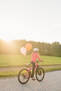 Sweden, Vastmanland, Hallefors, Bergslagen, Girl (10-11) riding bicycle at sunsetの写真素材 [FYI02856894]