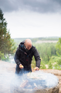 A man cooking on a campfireの写真素材 [FYI02856899]