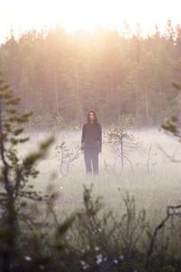 Woman standing in misty fieldの写真素材 [FYI02856914]