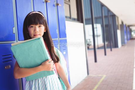 Portrait of elementary girl holding books in corridorの写真素材 [FYI02856961]
