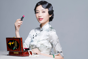 Young beautiful woman in traditional cheongsam holding a lipstickの写真素材 [FYI02856974]