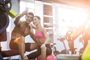 Young couple taking self portrait in the gymの写真素材 [FYI02856979]