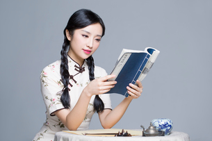 Young beautiful woman in traditional cheongsam reading bookの写真素材 [FYI02856994]