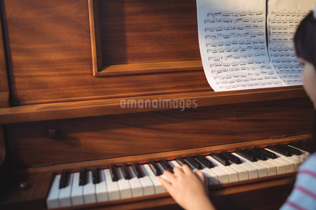 Cropped image of girl practicing pianoの写真素材 [FYI02857001]