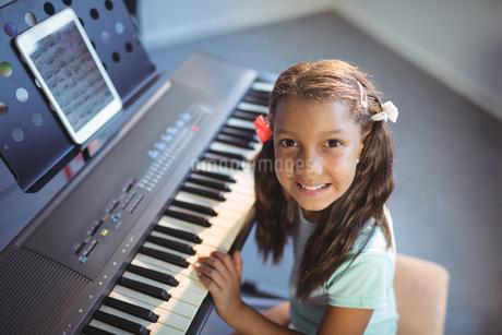 Portrait of elementary girl practicing pianoの写真素材 [FYI02857007]
