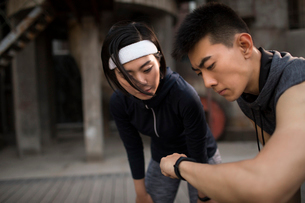 Young Chinese couple checking smart watch after runningの写真素材 [FYI02857010]
