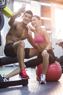 Young couple taking self portrait in the gymの写真素材 [FYI02857017]