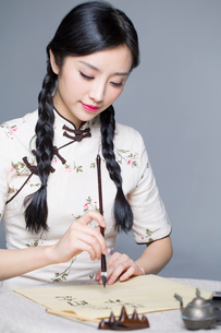 Young beautiful woman in traditional cheongsam practicing calligraphyの写真素材 [FYI02857024]