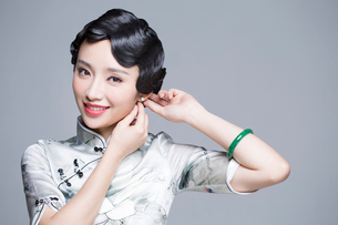 Young beautiful woman in traditional cheongsam dressing up herselfの写真素材 [FYI02857025]