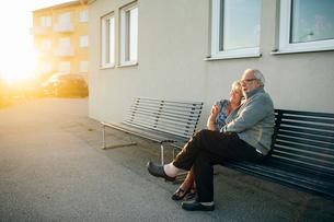 Senior couple hugging on benchの写真素材 [FYI02857037]